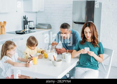 famille utilisant des smartphones tout en étant assis à la table de cuisine près du petit déjeuner servi Banque D'Images