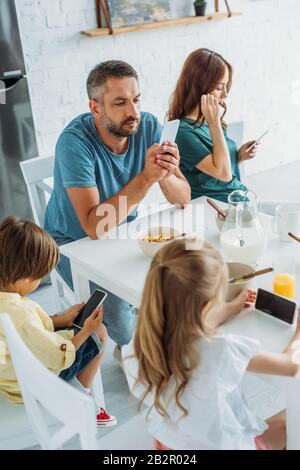 famille assis à la table de cuisine près du petit déjeuner servi et à l'aide de smartphones Banque D'Images