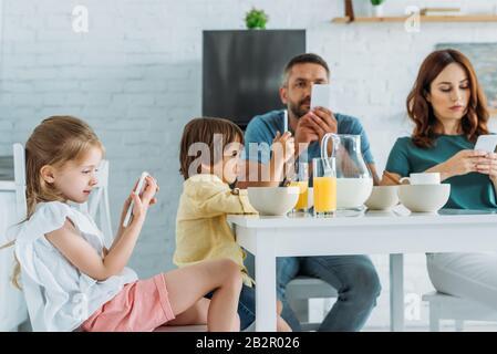 famille utilisant des smartphones tout en étant assis dans la cuisine près de la table avec petit déjeuner servi Banque D'Images