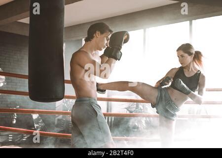 Boxe couple sportif musclé jeune homme et femme boxe ensemble contre fond lumineux. Banque D'Images