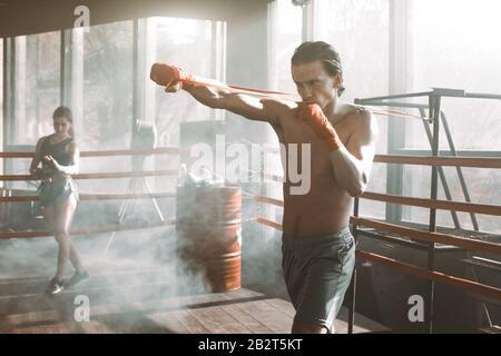 Beau homme travaillant avec un groupe de résistance dans le ring de boxe à la salle de gym. Bras et muscles du dos parfaitement façonnés. Banque D'Images