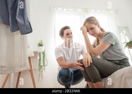 Jeune homme caucasien réconfortant à la triste femme déprimée assise sur le lit dans la chambre, la finance fail et le concept concerné. Banque D'Images