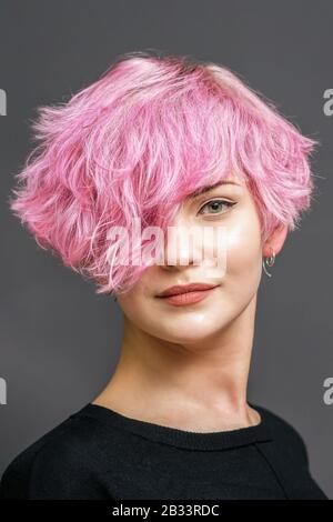 Portrait d'une jeune femme avec nouvelle coiffure rose courte sur fond gris.