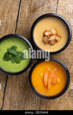 Variété de différentes soupes de crème végétalienne colorées dans des récipients alimentaires, vue de dessus Banque D'Images