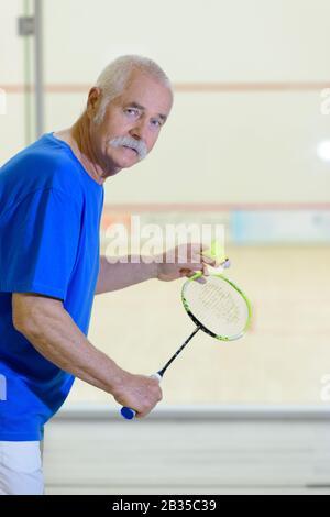 homme âgé faisant un service de badminton Banque D'Images