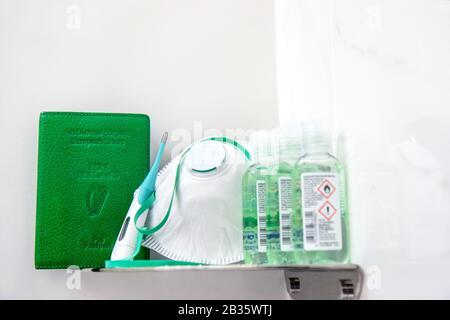 Coronavirus Covid-19 Irlande. Couvercle vert irlandais pour passeport sur étagère à côté du masque respiratoire, des bouteilles de gel désinfectant pour les mains et un thermomètre vert Banque D'Images