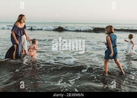 Mère forte avec quatre filles jouant dans l'océan au coucher du soleil