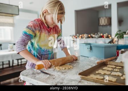 Petite fille qui roule la pâte à biscuits vue latérale Banque D'Images