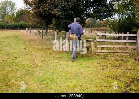 Walker croisant la ligne de clôture sur un chemin public à l'extérieur de Bibury, en Angleterre dans les Cotswolds. Banque D'Images