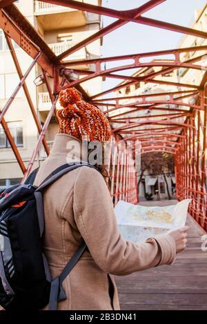 Femme touriste en regardant la carte sur un pont de la ville européenne, voyage en Europe
