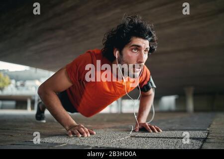 Un homme sportif jeune et déterminé à écouter de la musique sur l'oreillette en faisant des repoussez-les à l'extérieur