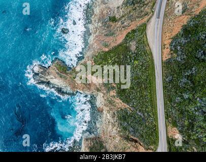 Vue aérienne des vagues qui se brisent sur la roche à côté d'une route. Mousse d'eau bleu clair et foncé pendant que les vagues se brisent sur le rivage. Mer profonde. Big Sur Cali
