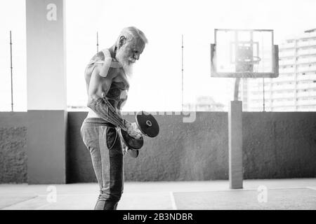 Homme de fitness senior faisant des biceps exercices de curl à l'intérieur de la vieille salle de gym - Fit mature entraînement masculin avec des haltères dans le centre de club de bien-être Banque D'Images