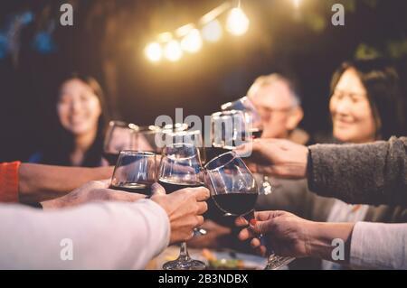 Bonne fête familiale avec du vin rouge au dîner de réunion dans le jardin - Senior ayant plaisir à griller des verres et à manger ensemble en plein air Banque D'Images