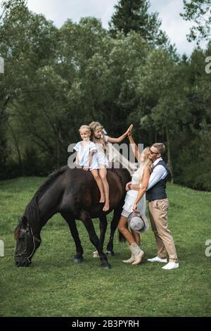 Famille aimante, père, mère et deux petites filles à cheval à la campagne en plein air. Jeune famille heureuse s'amuser, donnant cinq à chacun Banque D'Images