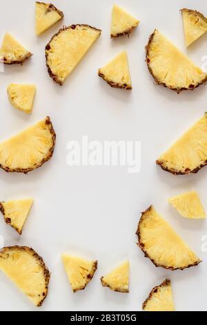 Plat lumineux avec des tranches d'ananas sur un fond blanc et un espace de copie au milieu Banque D'Images