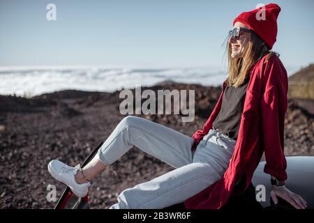 Portrait de style de vie d'une femme élégante vêtue d'une chemise rouge et d'un chapeau profitant d'un beau coucher de soleil au-dessus des nuages, voyageant en voiture sur les montagnes Banque D'Images