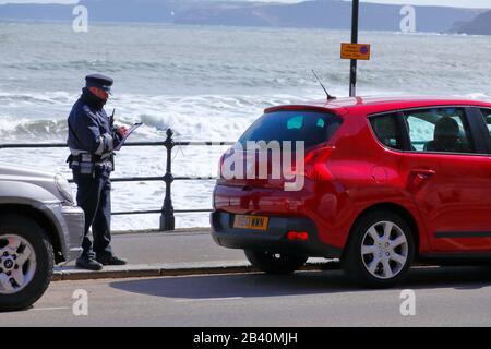 Un gardien de la circulation prépare un billet pour une voiture garée illégalement. Banque D'Images