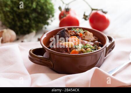 Cassoulet. Contenant des saucisses de porc à la viande, des oies, des canards et parfois des mutons et deux types de haricots blancs. Cuisine française (cuisine). Sur un vieux ba blanc en bois Banque D'Images