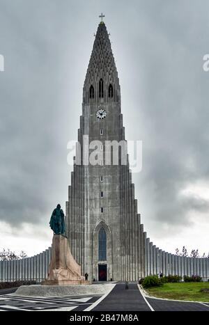 Europe, Islande , Statue de Leif Erikson, explorateur historique devant la spire futuriste et des colonnes en béton de Hallgrimskirkja, l'emblématique église luthérienne de Reykjavik Banque D'Images