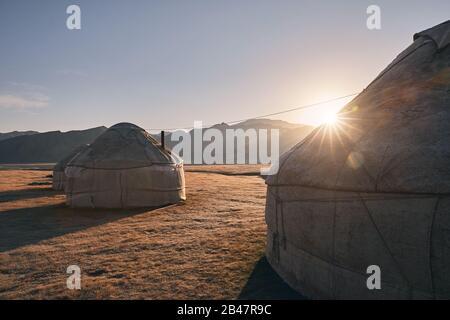Des maisons nomades yourtes campent dans la vallée de la montagne au lever du soleil en Asie centrale Banque D'Images