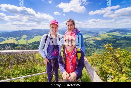Famille heureuse - mère et deux filles - lors d'un voyage de randonnée dans les montagnes - au sommet d'une montagne avec ciel bleu et nuages en arrière-plan Banque D'Images