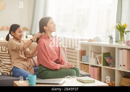 Photo horizontale de heureuse jeune fille de sitting sur le canapé dans le salon confortable tressant les cheveux de sa mère, espace de copie Banque D'Images
