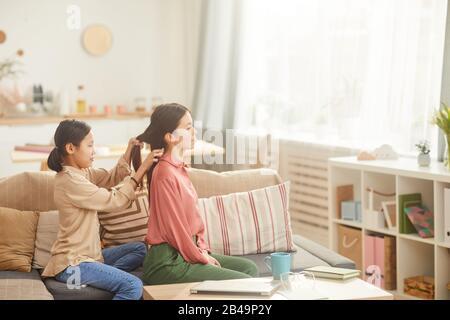 Vue latérale horizontale prise de vue d'une jeune fille sur un canapé dans le salon confortable tressant les cheveux de sa mère Banque D'Images