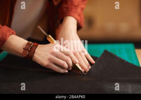 Jeune femme artisanale imreconnaissable découpant un morceau de cuir, gros plan horizontal Banque D'Images