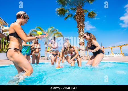 Joyeuse et amitié avec les femmes qui s'amusent avec des pistolets à eau dans la piscine - vacances d'été concept dans le complexe - voyage style de vie pour heureux âge moyen