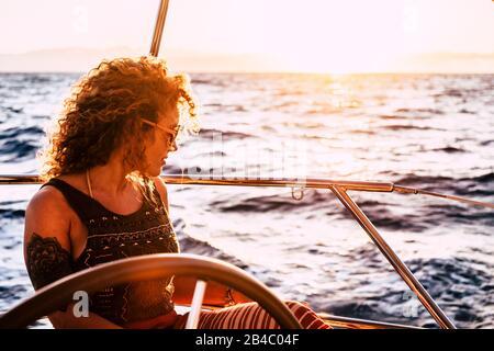 Belle jolie femme adulte blonde curieuse regardant l'océan en profitant d'un voyage et de Voyage sur le bateau à voile - les gens de génération moderne jouissent de la liberté et de style de vie alternatif voyager