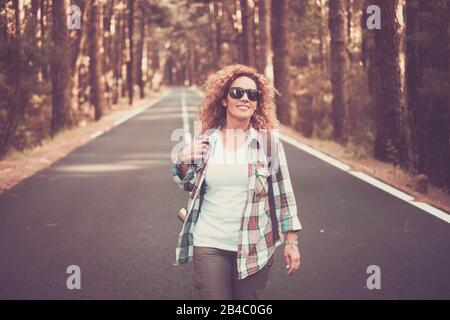 Joyeuses et joyeuses femmes voyagent gratuitement les gens qui marchent au milieu d'une longue route avec forêt et arbres autour - concept de voyage pittoresque - belle cacacasien curieusement femme profitant de l'activité de loisirs en plein air