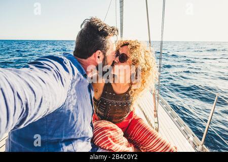 Couple de voyageurs adultes amoureux sur un bateau à voile - les gens qui apprécient les vacances d'été faire un voyage - activité de loisirs en plein air autre style de vie homme et femme embrassant et aimant avec la mer autour Banque D'Images