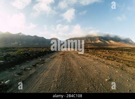 Route tout-terrain vue depuis le niveau du sol avec montagnes et ciel bleu nuageux - concept de voyage et d'aventure pour des vacances et le style de vie alternatifs