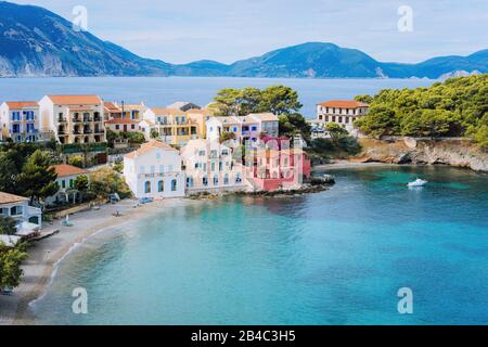 Jolie baie de mer bleue en face du village d'Assos. Belle vue sur des maisons colorées vives près de bleu turquoise couleur lagon transparent de baie. Kefalonia, Grèce. Banque D'Images