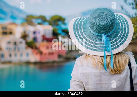 Vue arrière de la femme de tourisme porter un chapeau bleu de soleil et des vêtements blancs admirez la vue sur les maisons colorées et colorées du village d'Assos le jour ensoleillé. Visite de Kefalonia en été. Vacances de voyage en Grèce. Banque D'Images