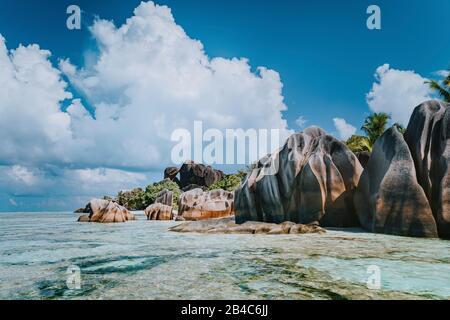 Célèbres rochers de granit dans le lagon avec eau peu profonde et paysage de nuages blancs sur l'incroyable plage tropicale d'Anse Source d'argent, la Digue Seychelles. Concept de voyage exotique de luxe.