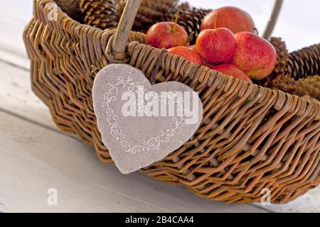 décoration rustique d'automne avec coeur en feutre sur un panier en osier avec pommes et cônes de pin Banque D'Images
