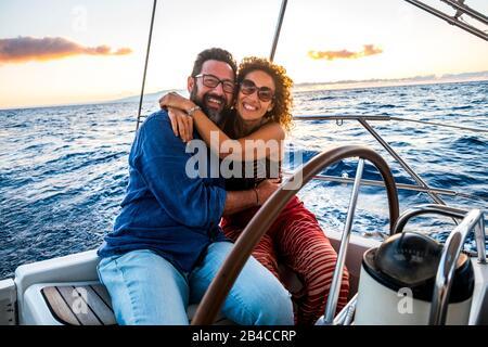 Heureux les personnes caucasiennes couple d'adultes profiter de la croisière en bateau à voile en vacances d'été - activité de loisirs en plein air avec l'océan et coucher de soleil en arrière-plan - voile avec amour et romance Banque D'Images