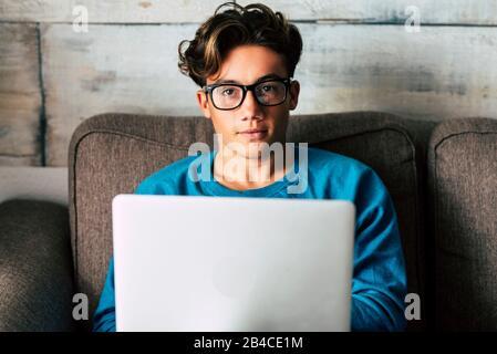 Portrait de beau caucasiens adolescent travaillant avec ordinateur portable personnel à la maison assis sur le canapé - concept d'étudiant pour le lycée ou diplômé ou la recherche d'emploi avec la technologie moderne