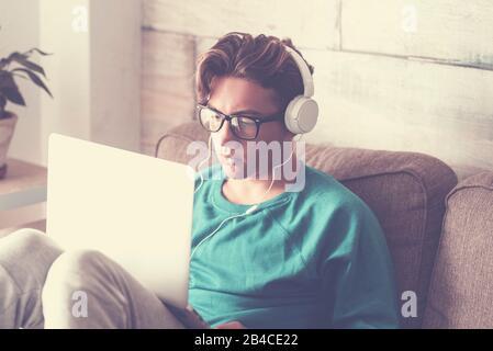 Jeune étudiant à la maison avec ordinateur portable moderne et casque étudiant avec connexion Internet - beau garçon assis sur le canapé avec technologie intérieure Banque D'Images