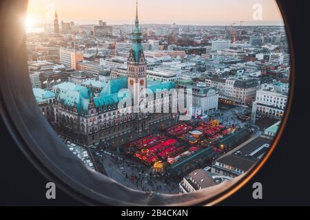 Vue de dessus du marché de Noël sur la place de la mairie à l'heure de l'avènement, Hambourg, Allemagne encadré dans la fenêtre de hublot.
