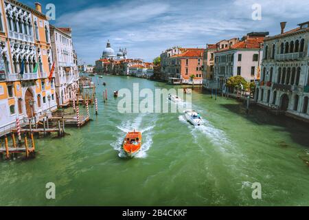 Des bateaux de tourisme de plaisir sur Grand Canal et basilique Santa Maria della Salute, Venise, Italie. Banque D'Images