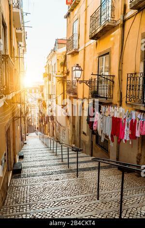 Escalier dans la rue pavée de Lisbonne. Blanchisserie suspendue dans une rue étroite typique. Coucher de soleil dans le vieux centre-ville de Lisbonne, impressions de la ville. Lissabon.