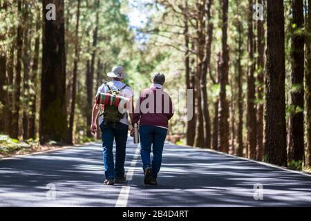 Voyage style de vie pour les vieux couple senior marchant ensemble au milieu de la route avec des arbres élevés sur les deux côtés - style de vie et togethness pour toujours concept de vie - personnes âgées