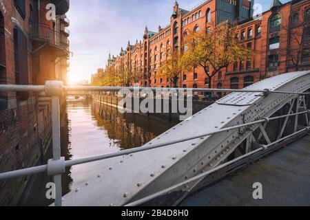 Pont d'arche sur les canaux dans le quartier historique des entrepôts de Hambourg, dans la lumière chaude du coucher du soleil, Allemagne, Europe