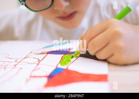 Enfant dessinant des formes abstraites sur un papier aux couleurs éclatantes. Introduction de la forme abstraite à travers l'ombre des objets dans la classe d'éducation artistique à l'école