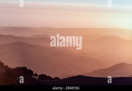 Coucher de soleil brumeux des collines californiennes : lorsque le soleil se couche sur la campagne vallonnée du sud de la Californie, les couches de collines disparaissent au loin. Banque D'Images