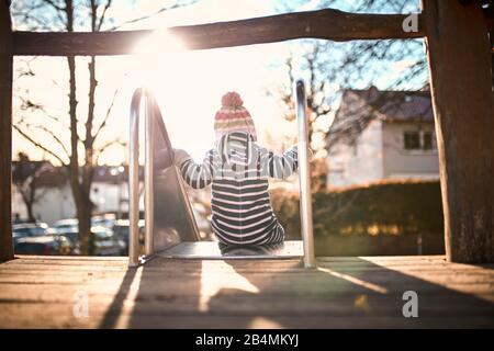Petit enfant sur un toboggan dans la lumière du soleil, de derrière Banque D'Images