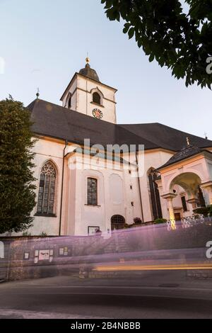 Vue à bas angle d'une église de St Wolfgang, Autriche avec des vitraux et un clocher flanqué d'arbres verts